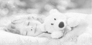 Petite fille endormie dans l'herbe avec son ours en peluche